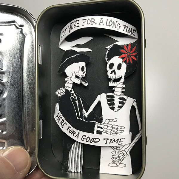 Paper cutout skeletons celebrating in an Altoids tin