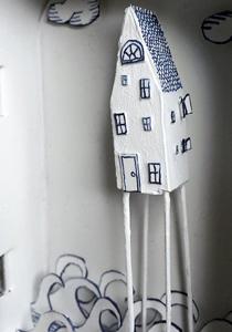 Altoid tin with house on stilts over the sea