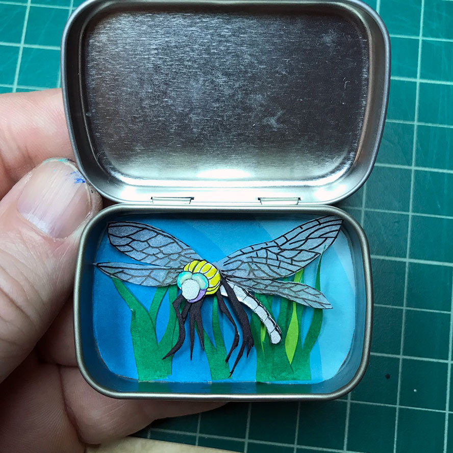 multi-layer cut paper dragonfly in an Altoids Smalls tin