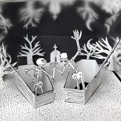 A cut-paper graveyard in a metal tea tin