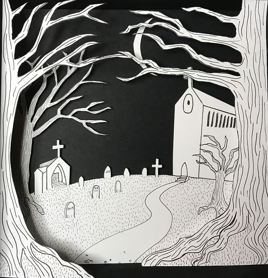 A black and white cut paper church and graveyard