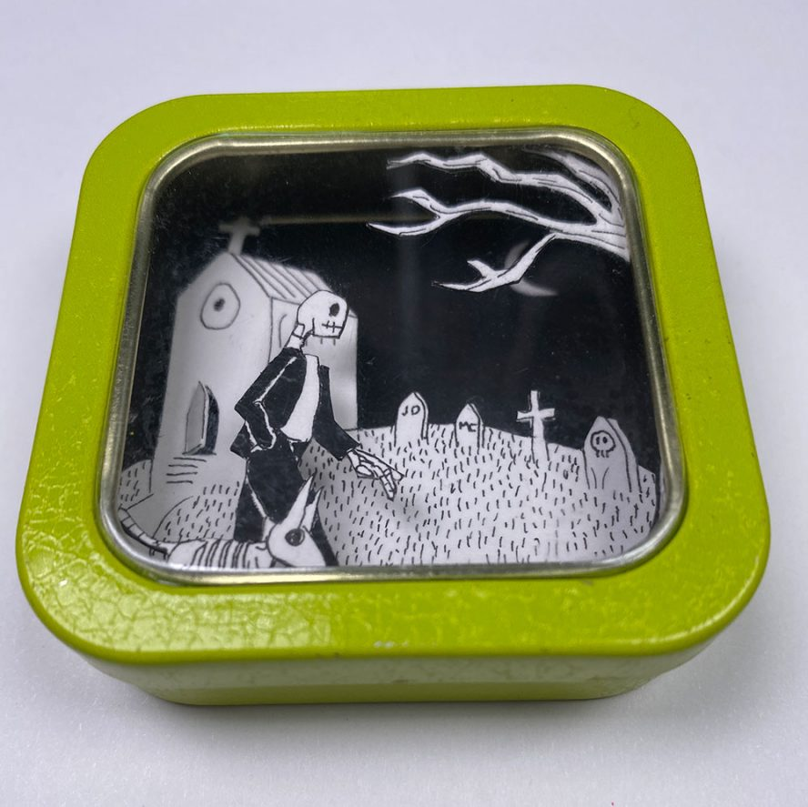 "Cut Paper Diorama in 2"" box, A skeleton and dog walking"