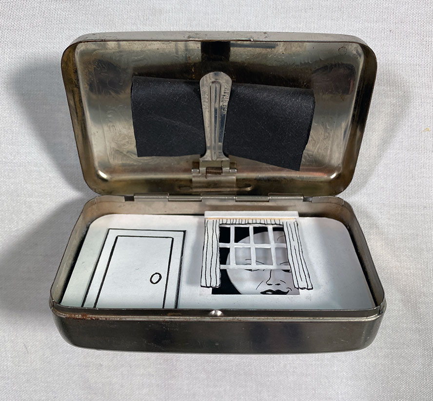 Silver box half open, showing diorama inside