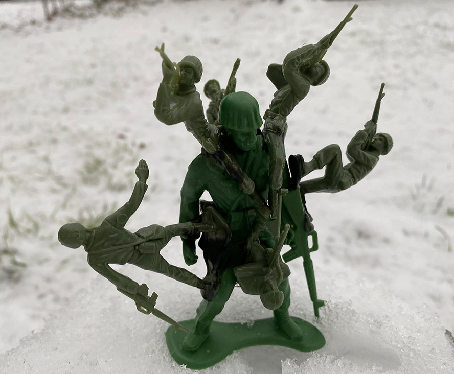 Large plastic army man with smaller army men attached to him.