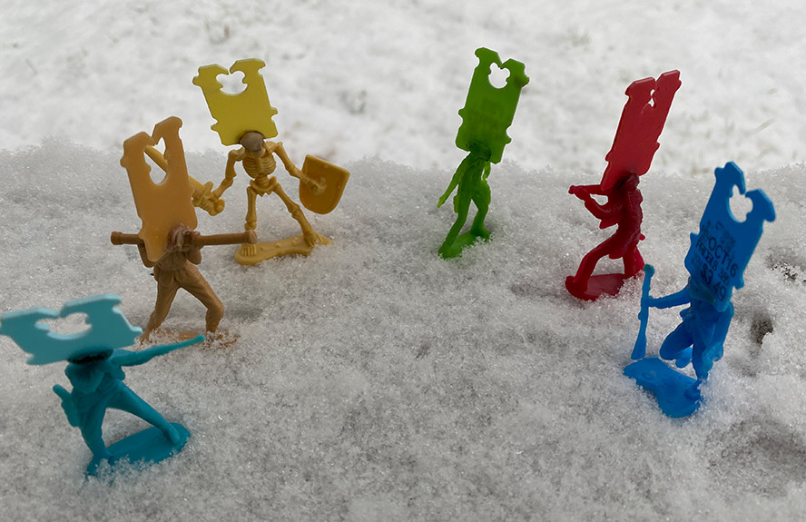 Plastic figures arrayed in a half circle in the snow