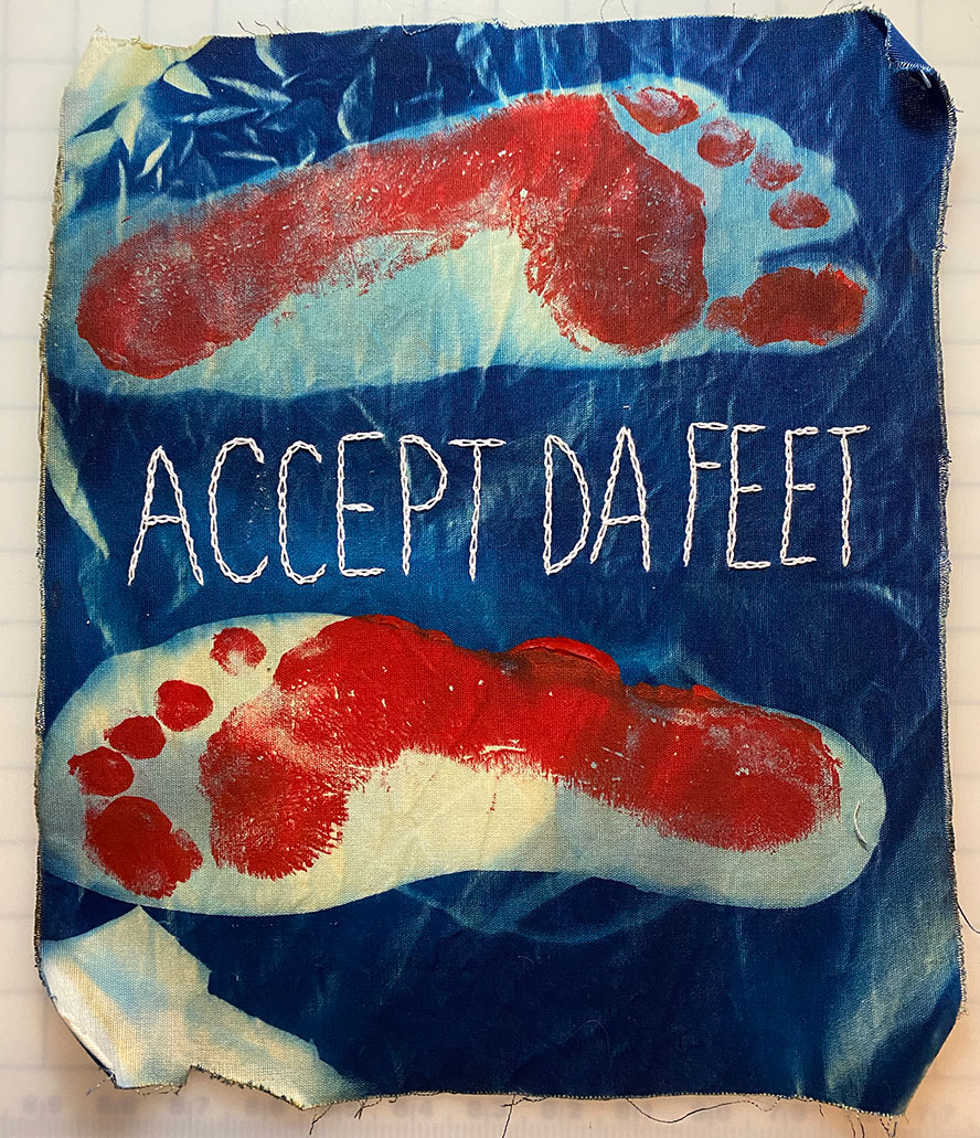 Cyanotype exposure on cloth, with red footprints in the outlines of a foot and shoe. Embroidery reads ACCEPT DA FEET