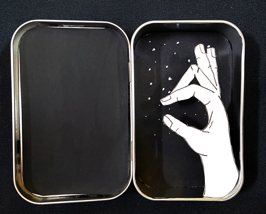 A cut paper hand making a shadow animal in a metal tin.