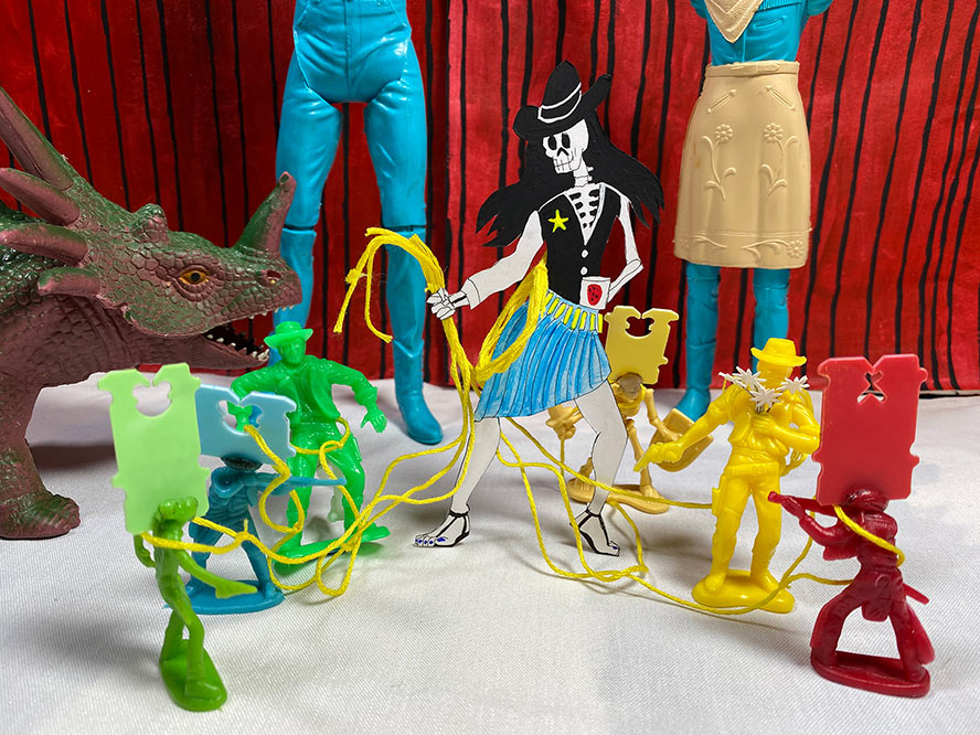 A skeleton cowgirl lassoing a bunch of plastic action figures.