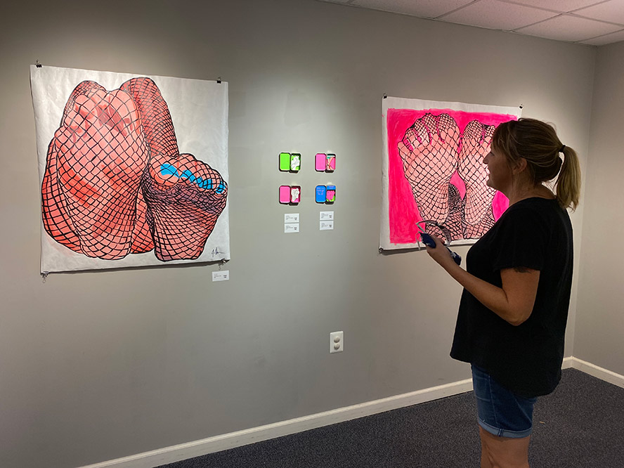 Woman looking at drawings in a gallery